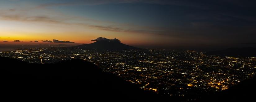 Il sole tramonta, il Vesuvio riposa, la città vive.